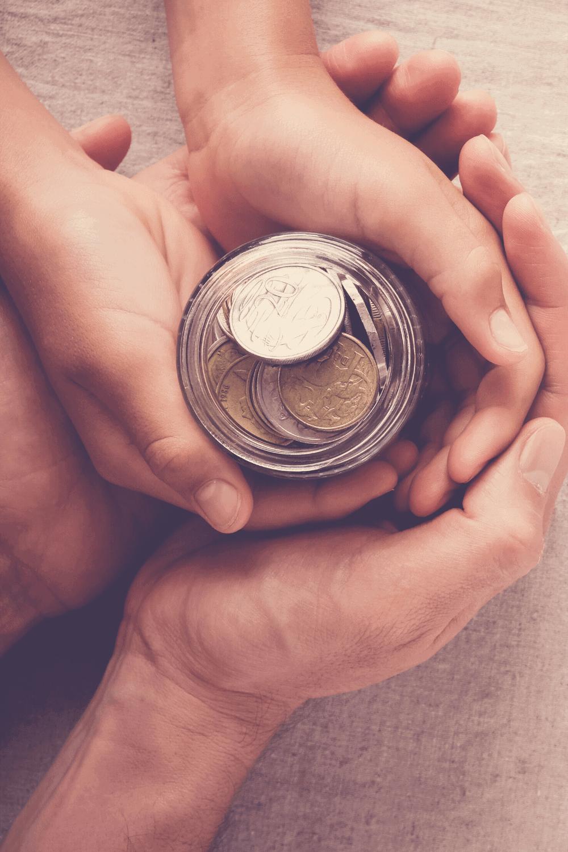 hands holding change jar