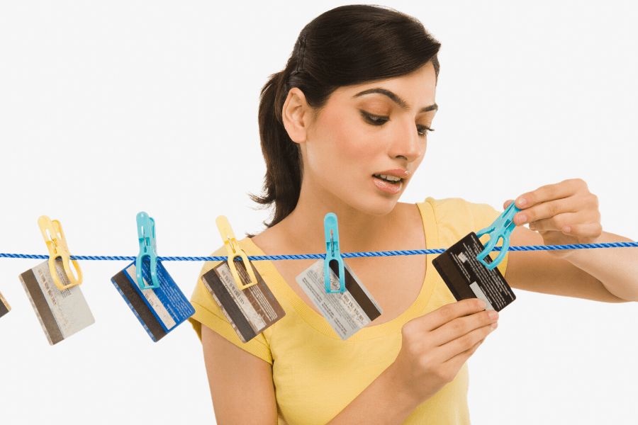woman pinning credit cards to a clothesline
