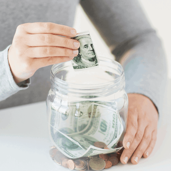woman putting money in a jar